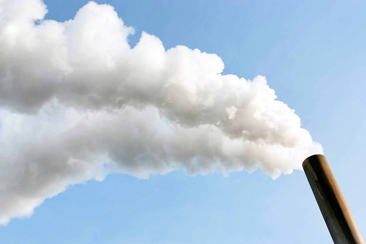 smoke billowing from a chimney, a type of environmental pollutant that can cause free radicals when it gets into your system