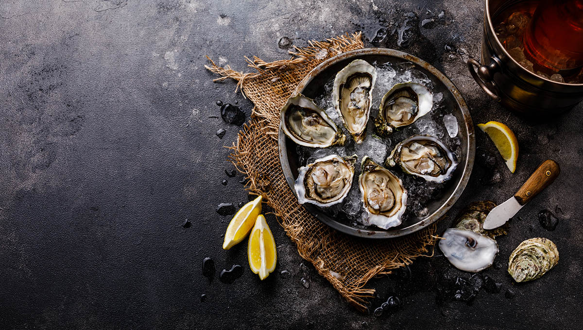 Open shucked fresh Oysters — a good source of zinc — with lemon and Rose Wine in ice bucket on dark background copy space