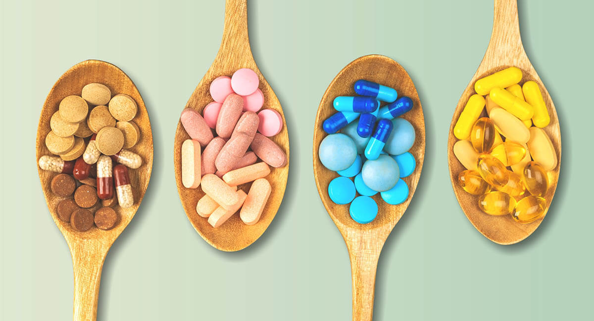 vitamin pills on wooden spoons
