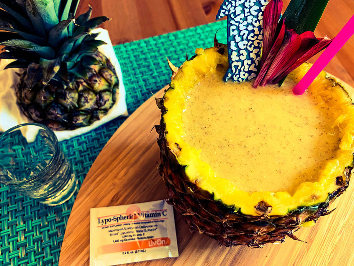 overhead photo of the immuni-tiki immune support smoothie in a pineapple with a packet of lypo-spheric vitamin c
