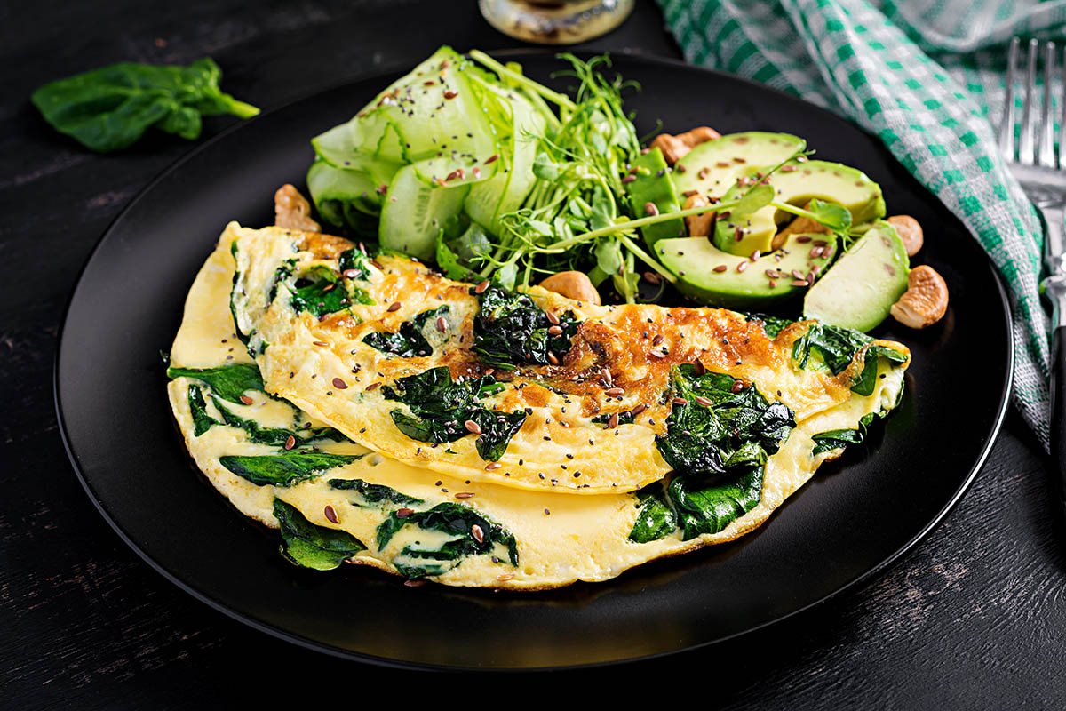 Omelette with spinach along with avocado and cucumber illustrates nutrient pairings for vitamin absorption