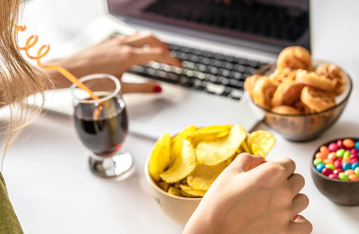 Girl works at a computer and eats unhealthy, processed food while drinking wine, all of which weaken the immune system