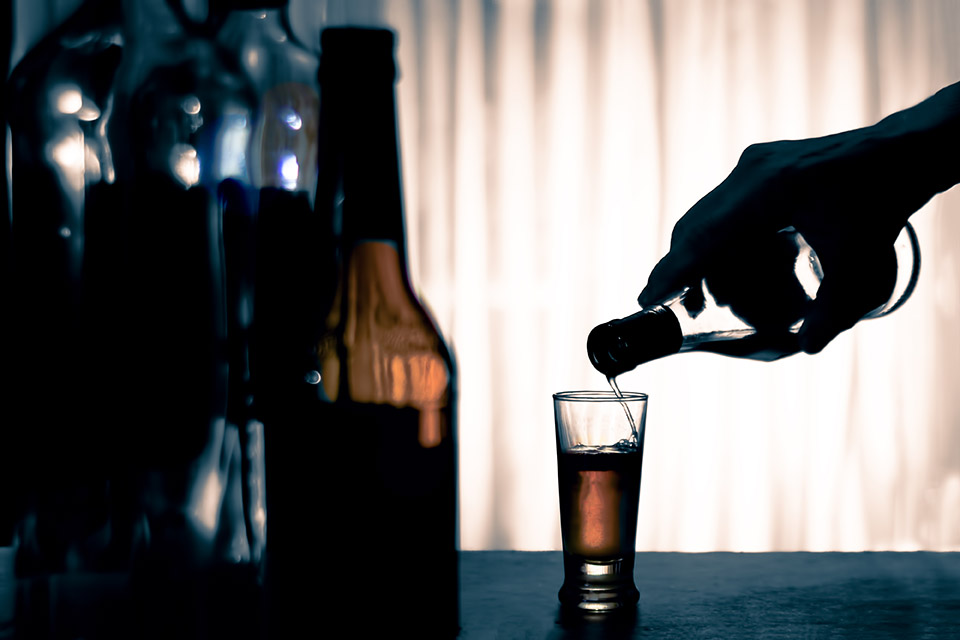 hand pouring alcohol, which can deplete vitamins when consumed chronically