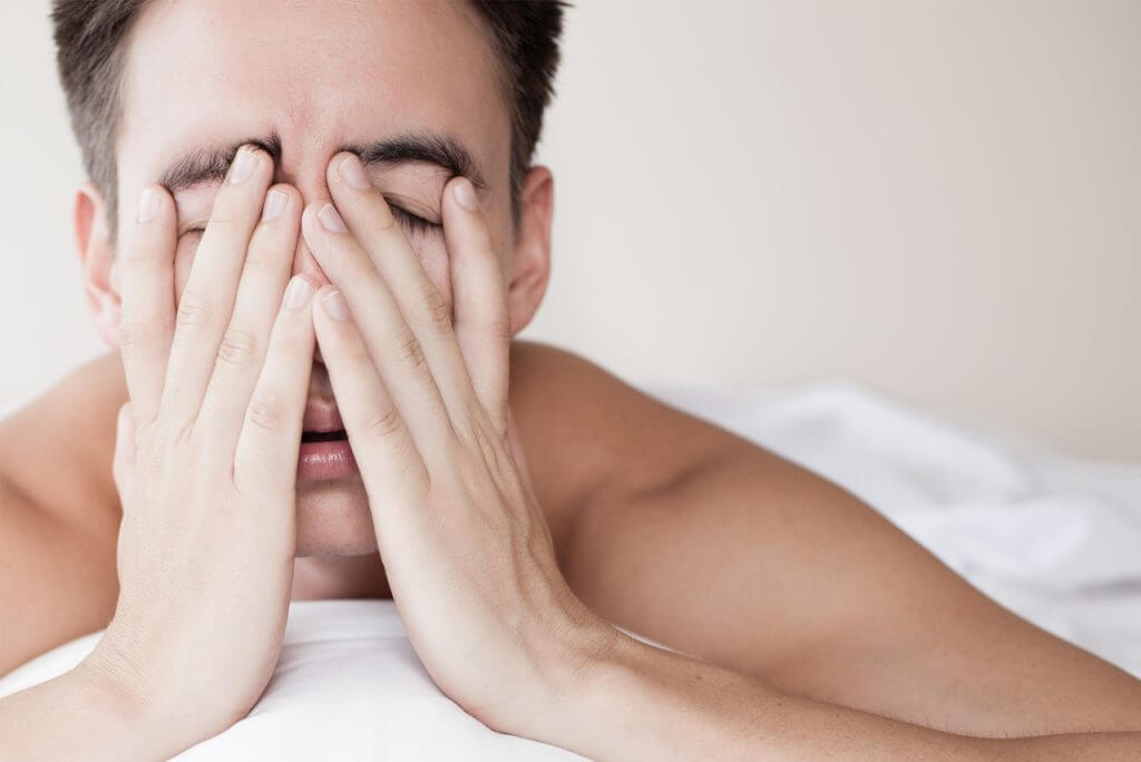 man looking tired in bed
