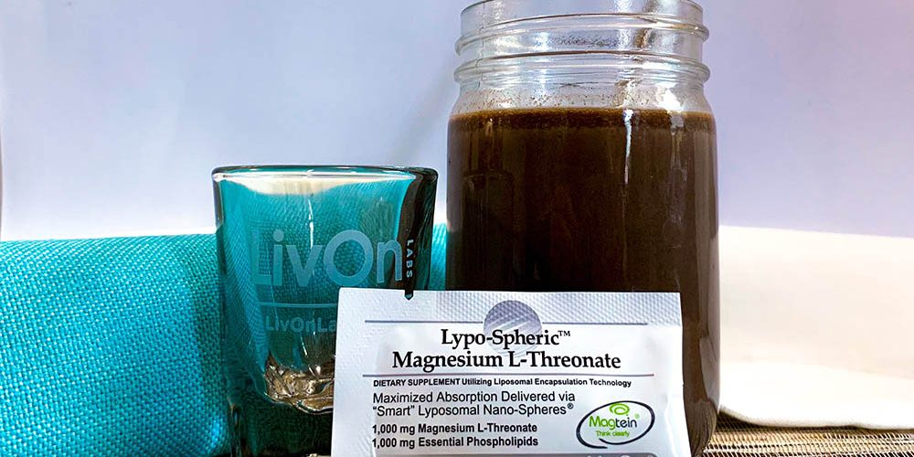 packet of lypo-spheric magnesium l-threonate with a shot glass and mason jar filled with cognitive cocoa
