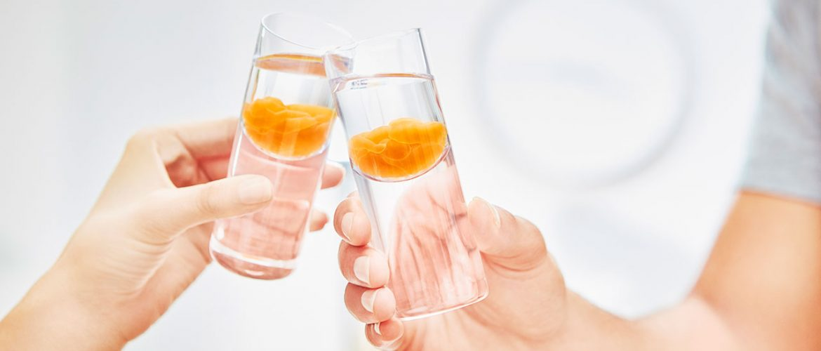 two people toasting with shot glasses containing LivOn Labs liposomal supplements