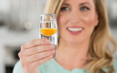 woman holding shot of lypo-spheric vitamin c