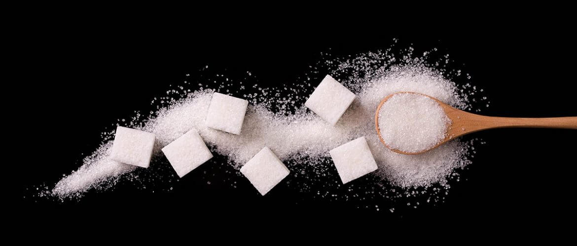 Sugar scattered from wooden spoons on a black background. Excess sugar like in these cubes can deplete vitamins and minerals