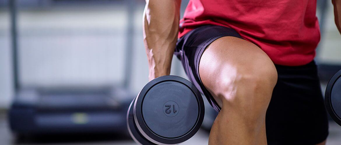 man lunging with dumbbells may take vitamins for muscle growth