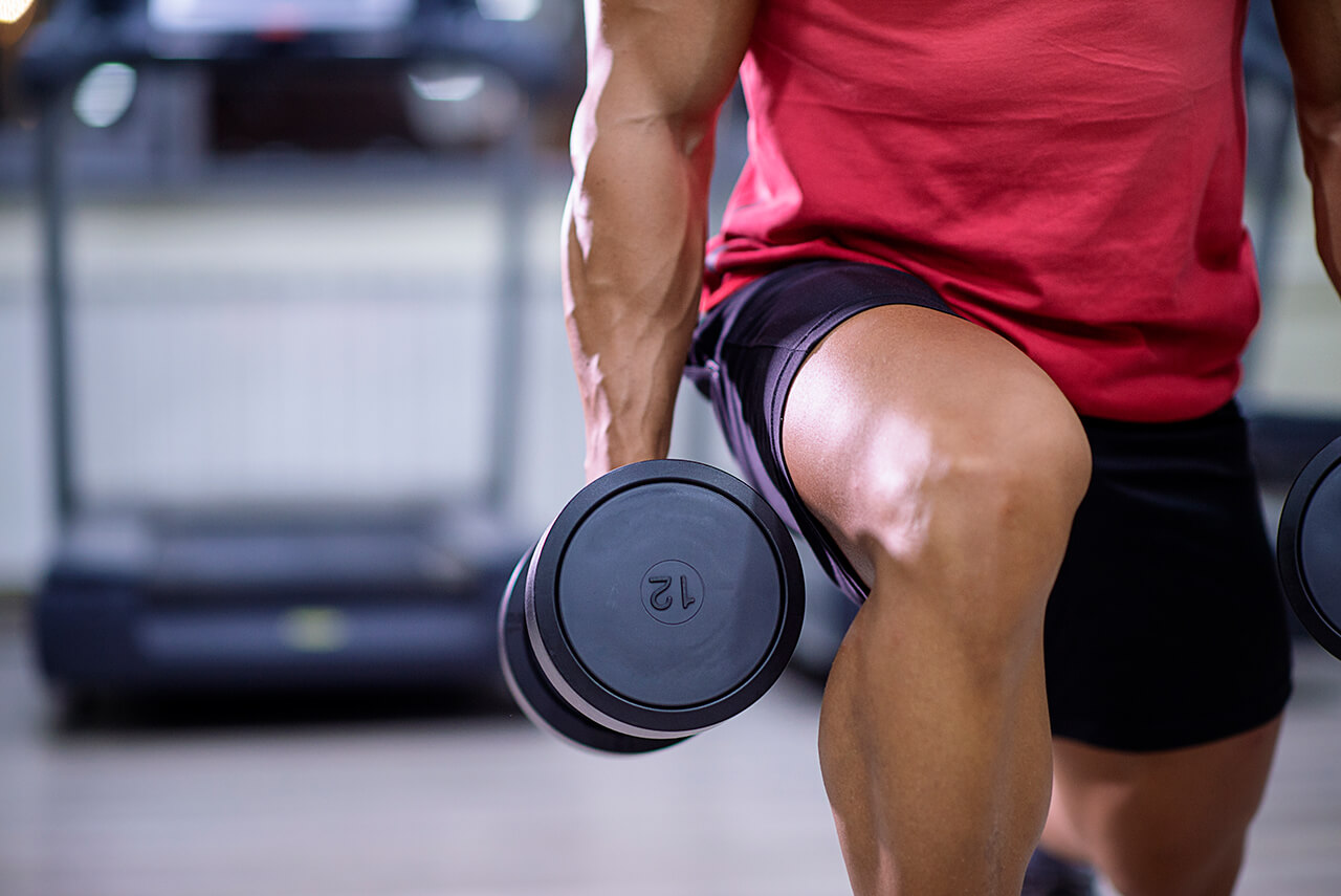 man lunging with dumbbells at the gym may consider vitamins for muscle growth