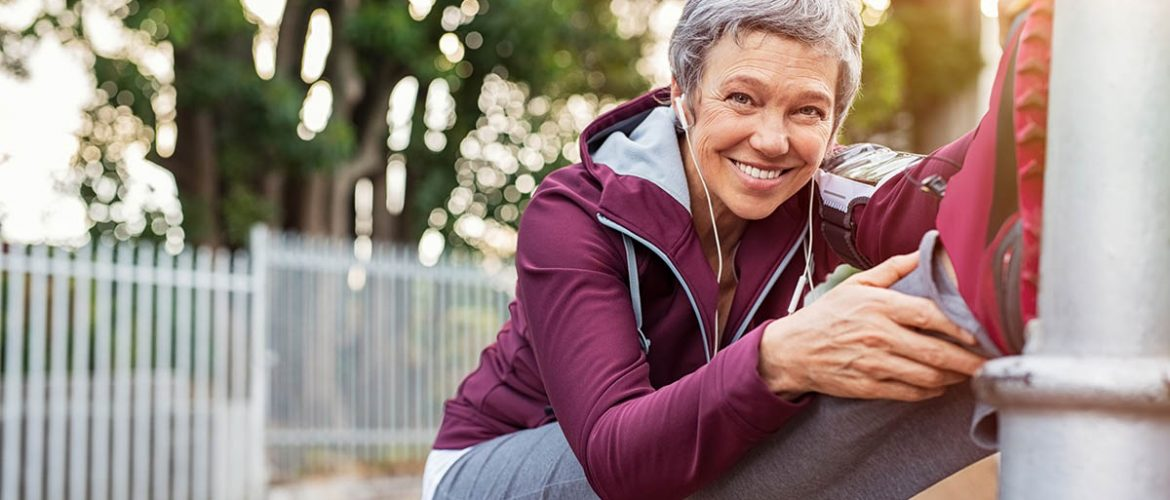 Smiling retired woman listening to music while stretching legs outdoors. Senior woman enjoying daily routine warming up before running at morning. Sporty lady doing leg stretches before workout and looking at camera.