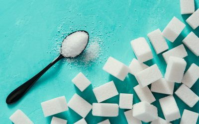 Top view of white sugar cubes on turquoise background